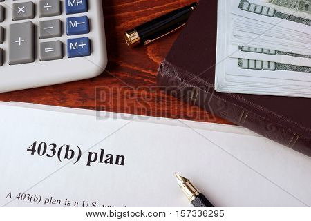 Papers with 403(b) Plan and book on a table.