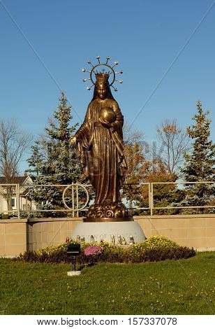 A close-up image of a bronze statue of the Mother Mary on the entrance of a catholic cemetery.