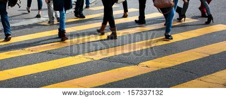 urban traffic concept - city street with a motion blurred crowd crossing a road