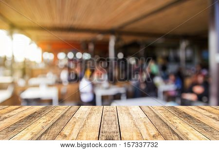 Selected focus perspective wood table and coffee shop blur background with bokeh image. for your photomontage or product display.