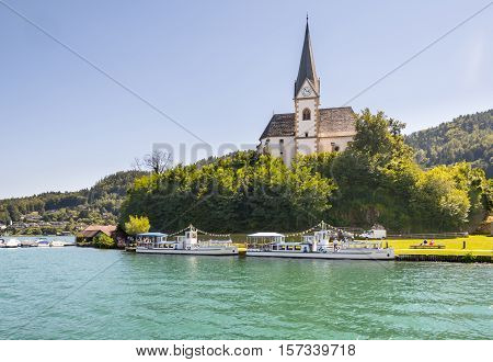 Maria Worth Austria - August 14 2016: Vintage tourist boats at the church of Maria Worth waiting for passengers. Saints Primus and Felician Church in the background is popular pilgrimage site.