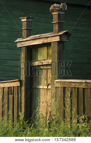 Wooden wicket and fence to the yard. cat sleeping on the gate.