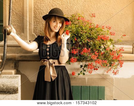 Portrait of young romantic woman outdoors. Retro styling fashion girl in black hat and dress on street of the old town city Gdansk Danzig Poland