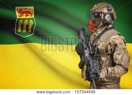 Soldier In Helmet Holding Machine Gun With Canadian Province Flag On Background Series - Saskatchewa