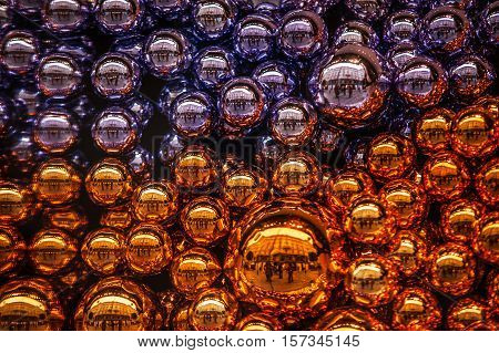 Filled frame composition with colorful Christmas balls of orange and purple color. Selective focus