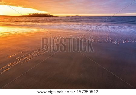 Sunrise at Popham State beach Maine. With Long exposure and Golden light casting upon the waves and sandy beach