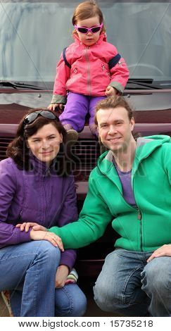 Happy family in outwear, mother and father hunker down in front of car and their little daughter sitting on car in sunglasses, focus on parent