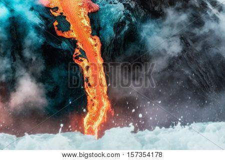 Narrow stream of molten lava flows into Pacific Ocean on Big Island of Hawaii