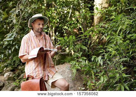 Serious And Concentrated Scientist With Leather Bag And Manual In His Hand Reading Information About