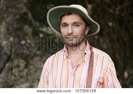 Headshot Of Attractive Scientist With Stubble Standing Outdoors At Rocks While Conducting Scientific