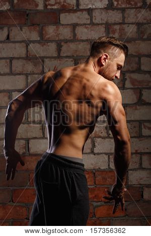 Bodybuilder posing at a brick wall. The athlete ahead of the competition. Drying. Relief and sculptural body muscles. Concept of healthy life. Dorsi.