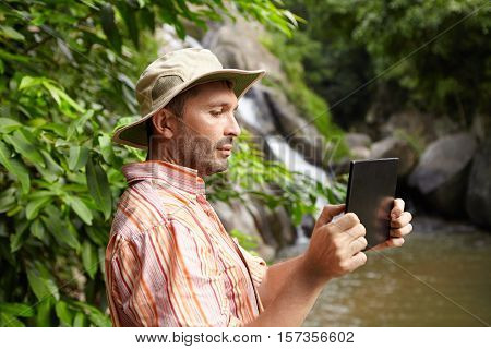 People And Technology Concept. Side View Of Bearded Ecologist In Panama Hat Taking Photographs Or Sh