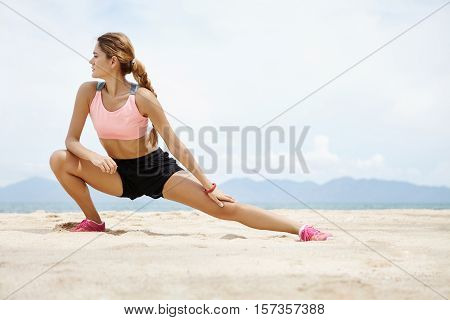 Fitness And Motivation. Healthy Athlete Girl Stretching On Beach On Sunny Day. Sporty Female Woman W