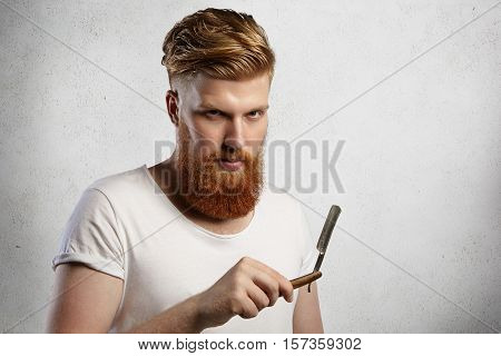 Handsome Barber With Thick Beard Holding His Barbershop Accessory, Demonstrating Sharp Blade Of Stra