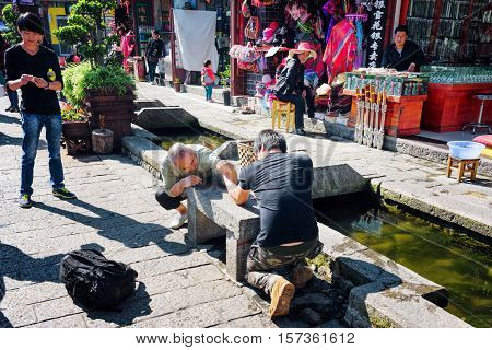 Arm Wrestling Fight On Stone Bench In Dali Old Town, China