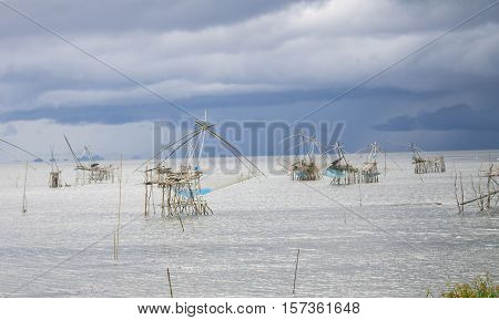 Pak Pra lakePattalungThailand. traditional fishing method using a bamboo square dip net with storm clouds.