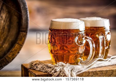 Beer. Two cold beers. Draft beer. Draft ale. Golden beer. Golden ale. Two gold beer with froth on top. Draft cold beer in glass jars in home pub hotel or restaurant. Still life.