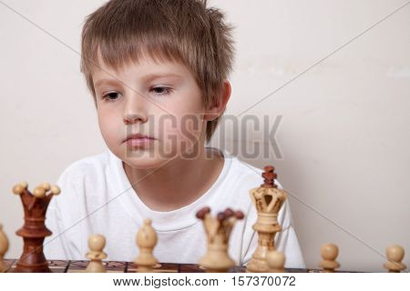 Portrait of a clever boy playing chess