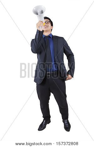 Asian businessman standing in the studio while speaking with a megaphone isolated on white background