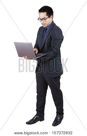 Full length of young businessman standing in the studio while wearing formal suit and using a laptop computer