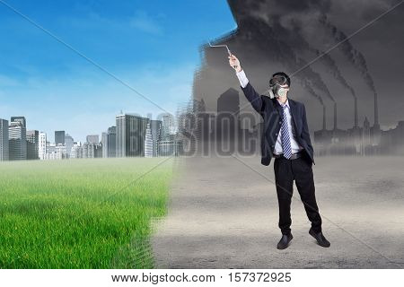 Image of a businessman wearing a gas mask and using a roller to change the grey city landscape into green city