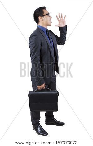 Full length of a young businessman carrying a briefcase and shouting in the studio isolated on white background