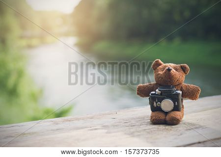 Teddy bear with camera with landscape view Vacation and travel concept
