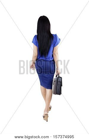 Back view of a female entrepreneur walking in the studio while carrying a briefcase isolated on white background