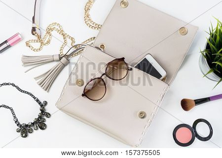 Fashion woman handbag with cellphone makeup and accessories Top view
