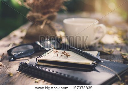 Notebook with cup of coffee on wooden table in the garden Vintage tone