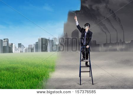 Businessperson wearing a gas mask and standing on a ladder while using a roller to change a polluted city into an environmentally friendly city