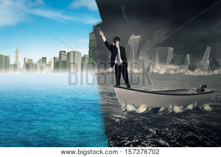 Businessman standing on a boat while using a roller to change a collapse city into a new city. Concept of an effort or change to success