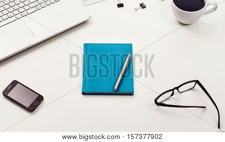 Top view of creative drawing or writing theme concept. Notepad or vintage callendar and crumpled paper on white, wooden table background.