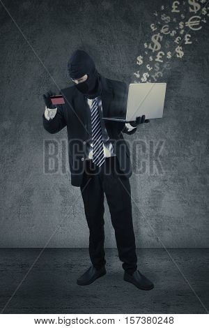 Male thief wearing a mask and holding a credit card with a laptop computer. Concept of hacker stealing a credit card information