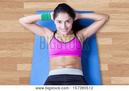 Beautiful indian woman wearing sportswear and doing sit ups on the mattress at home