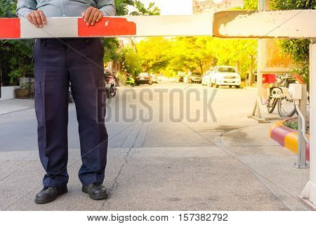 Security guard with barrier gate for access control at gateway process in soft orange sun light style
