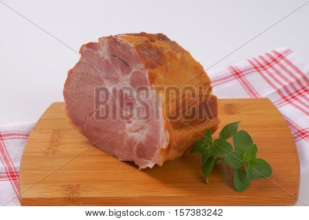 piece of smoked pork neck on wooden cutting board - close up