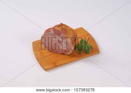 piece of smoked pork neck on wooden cutting board