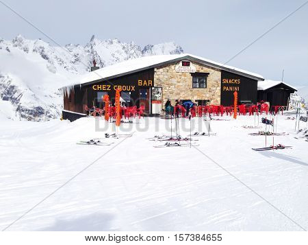 Courmayeur, Italy - January 27, 2015: Restaurant, skiers and snow mountain peaks at Courmayeur ski resort, Italy