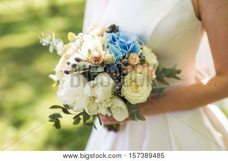 Closeup Photo Of Bride Holding A Flower Bouquet