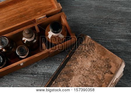 Vintage glass bottles in box with old book on wooden background, closeup