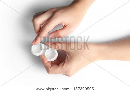 Close up view of female hands taking lens out of container on light background