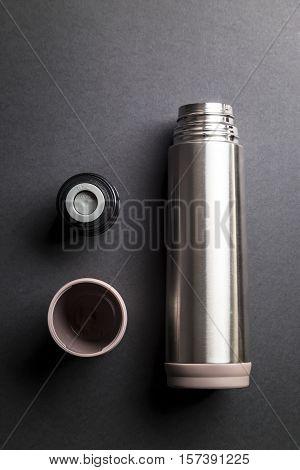 Metallic thermos over black background presentation .