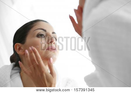 Adult woman applying cream on face in mirror reflection