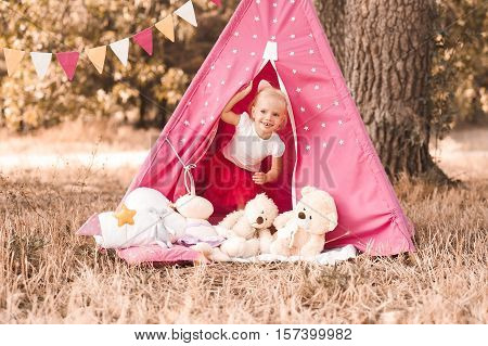 Funny baby girl 2-3 year old playing with toys in wigwam outdoors.Looking at camera. Childhood.