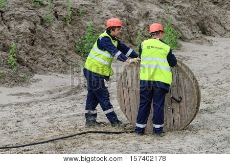 Tobolsk, Russia - July 15. 2016: Sibur company. Construction of plant on processing of hydrocarbons. Two workers pulling roll high voltage cable line