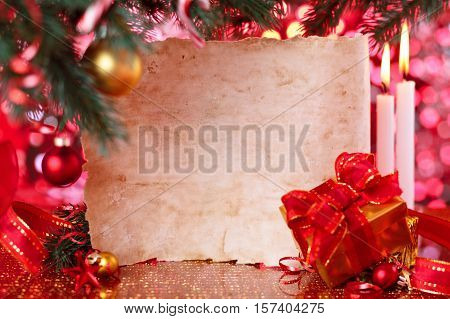 Gift and old parchment against Christmas background. Focus on parchment.