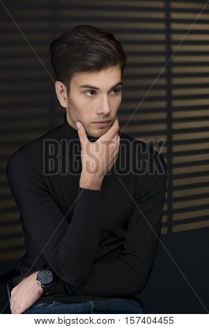 Stylish young man in a black sweater sits near blinds and thinking about something