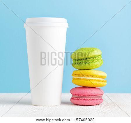 Macaron and tumbler of coffee. Closeup view.