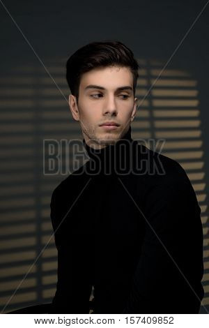 portrait of the young man against the background of blinds. the man longs in the evening and thinks